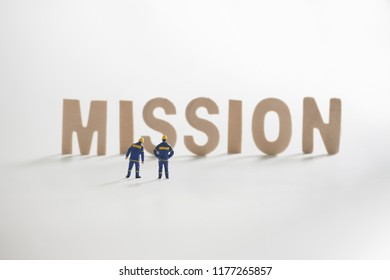 Miniature people: Engineer standing infront to seeing on MISSION word use as businessconcept concept.