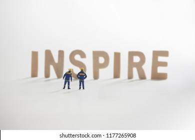 Miniature people: Engineer standing infront to seeing on INSPIRE word use as business and inovation concept.