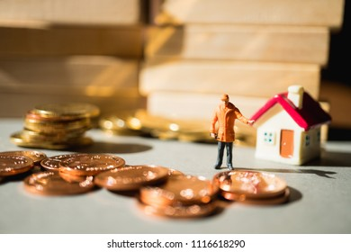 Miniature people, engineer standing with stack coins and mini house using as business, industry and financial concept