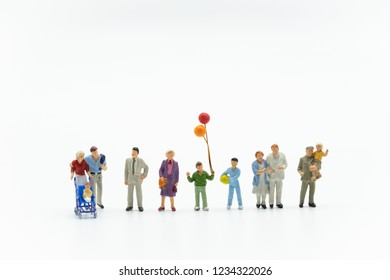 Miniature people, family and children with colorful balloons  standing isolated on white background. International Day of Families