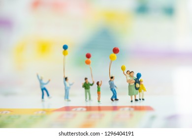 Miniature people, family and children with colorful balloons  standing. International Day of Families