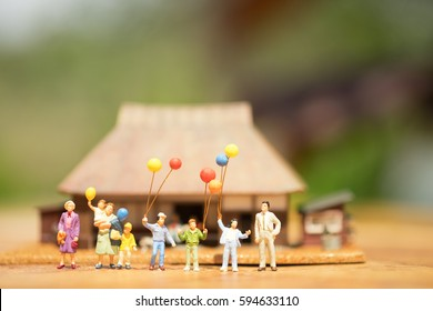 Miniature people, family and children with colorful balloons  standing in front of house. International Day of Families