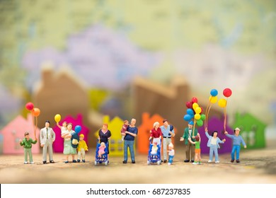 Miniature people, family and children with colorful ballons  standing in front of house. International Day of Families
