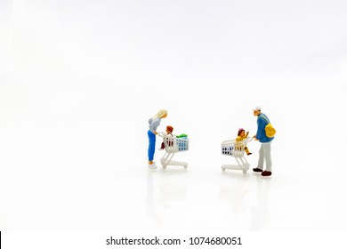 Miniature people: Family and children with shopping cart. Concept of tourism, shopping or business.
