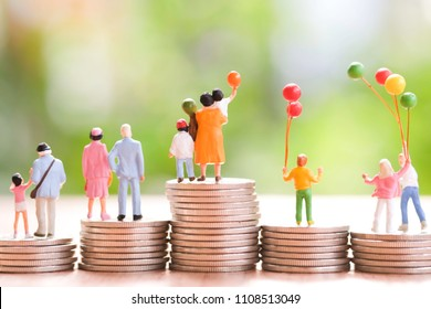 Miniature People : Family with colorful balloon stand on the stack of coins looking forward to the future use as business and happy holiday concept.