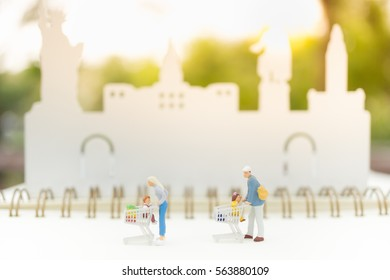 Miniature people : Family Mother, Father and children go shopping / buying using cart with Credit card background, spending money for supermarket goods concept