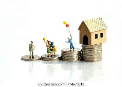 Miniature people: family standing with coins stacks with house model on the top stack. concepts. Concept for property ladder, mortgage,real estate investment, money, love and Valentine's day.