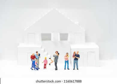 Miniature people, family standing in front of toy houses. Concept for property ladder, mortgage and real estate investment and lover.