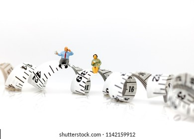 Miniature people: Fat people sitting on measure tape . Healthy lifestyle, dieting and obesity Concept