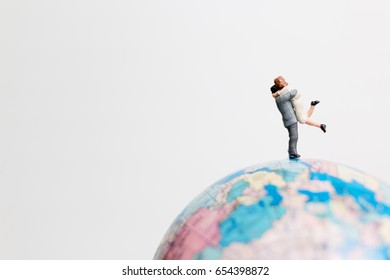 Miniature people figure  standing on the globe world map with white background and copy space as travel concept