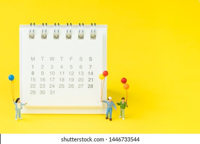 Miniature people figures happy family holding balloons standing with white clean desktop calendar on solid yellow background with copy space, schedule plan, reminder or special event date concept.