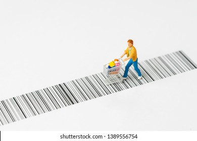 Miniature people figurine with grocery in the shopping cart or trolley rally on the bar code using as e-commerce with copy space, consumer or buy and sale in new technology channel concept.