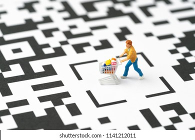 Miniature people figurine, a man with grocery in the shopping cart at the center of labyrinth QR code, ecommerce, consumer is mainly buy and sale in new innovation technology mobile channel.