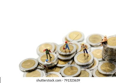 Miniature people : fisherman sitting and standing on stack coin, using for business concept.