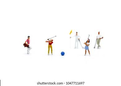 Miniature people : Golfer teams playing.