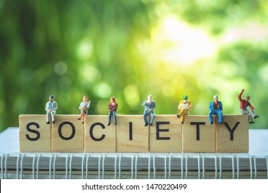 Miniature people, group of business people sitting on wooden blocks with SOCIETY word, doing activity and discussing ideas, society and teamwork concept.