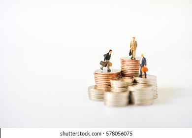 Miniature people: Group of Businessman figure standing on stack of coin. Business Money and Banking financial concepts.