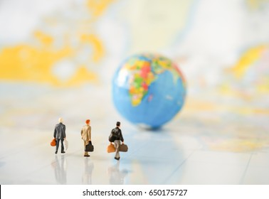 Miniature people: Group of Businessman mini figures walking to Global Balloon Map Model on world map with Copyspace. Success Business Due around the world and Travelling agency concepts.