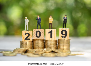 Miniature people: group of businessman on coins stacks with wooden block 2019 text as background, success, dealing, greeting and partner concept.