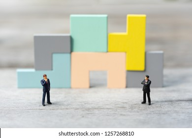 Miniature people: Group of businessmen making decision in front of wooden jigsaw puzzle icon, success, dealing, greeting and partner concept.