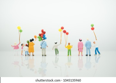 Miniature people : Group of family with balloon using as background learning and play, international family day concept.