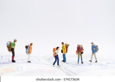Miniature people: Group of traveler miniature mini figures with backpack stand and walking on passport with stamps. Travelling concepts.