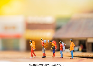 Miniature people: Group of traveler mini figures with backpack stand and walking on vintage map and blurred japanese town. Travelling concepts.