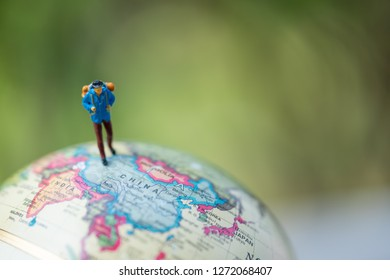 Miniature people: group of traveler on earth globe ,traveling around the world,  exploring on earth background concept.