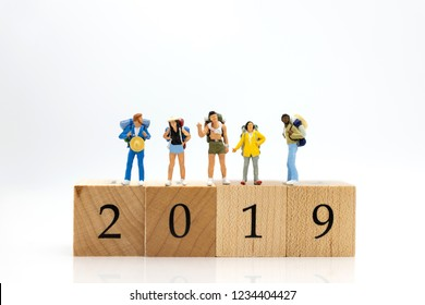 Miniature people, group travelers standing on wooden block 2019, new year. Image use for travel business concept.
