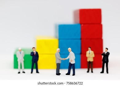 Miniature people handshake with step of Wood block stack.  agreement, investment, partnership and business concept