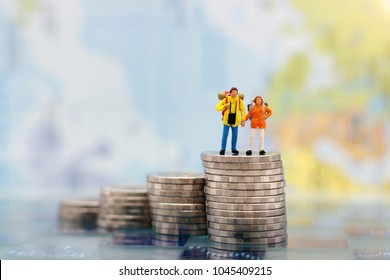 Miniature people: Happy couple backpacker standing on coins stack, money saving growth. Saving Money, Travel insurance,  Emergency plan  and Financial Concept.