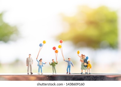 Miniature people : Happy family  with balloons ,   Happy family relations and carefree leisure time Concept