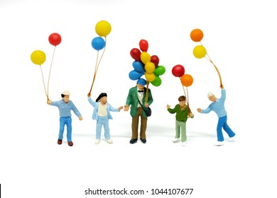 miniature people, Happy family and children enjoy with colorfull balloons standding on white blackground. Picture use for holliday concept.