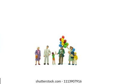 miniature people, Happy family and children enjoy with colorfull balloons. They are standding on white background. Picture use for holliday concept or international day of families.