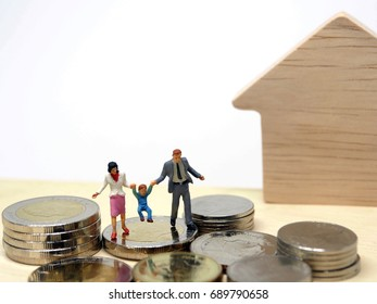 Miniature People Happy Family with Stack Coins on Table White Background Copy Space for Text : Saving Money, Insurance, Home Loan, Mortgage, Education and Real Estate Investment Concept.