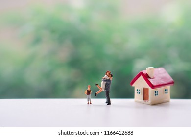 Miniature people, happy family standing with mini house using as family and property concept