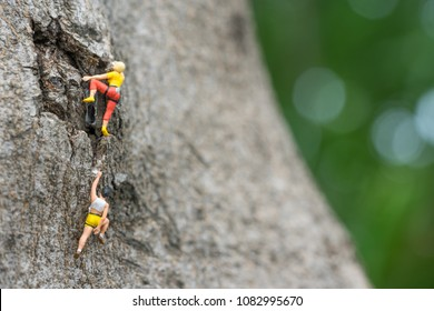 Miniature people, hikers climbing up on the mountain. Sport and leisure concept.