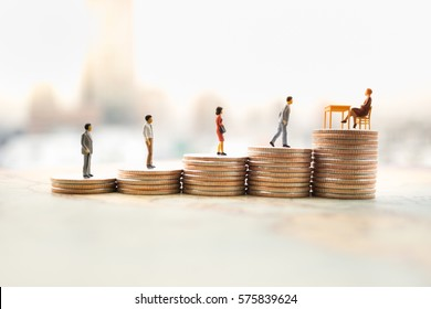 Miniature people: hire employment, employ interview concept. Candidate businessman  waiting/walking to interview with women sitting on top of coins stack.