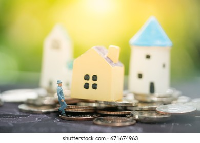 Miniature people with house model on coins stack using as background property ladder, mortgage and real estate investment concept.