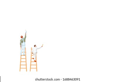 Miniature people with ladder holding brush in front of a white wall background