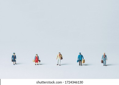 Miniature people lined up at intervals