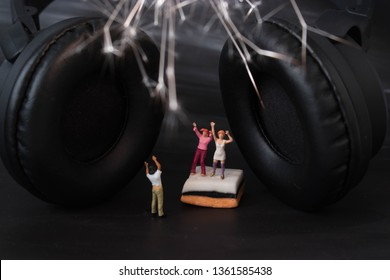Miniature people listening to loud music on wireless, noise cancelling headphones.Small group having a party with fireworks and music.High powered sound system for loud listening. Happy, young party.