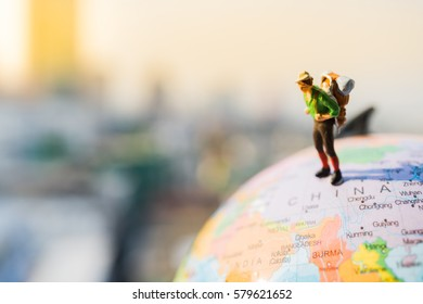 Miniature people: Lonely backpacker, mini figure, standing over China map on globe with modern city background. Agency marketing and Travelling concepts.