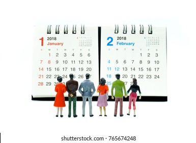 Miniature people looking at calender