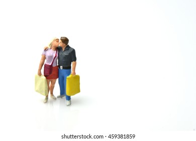 miniature people : the lover and shopping bag kissing on white background