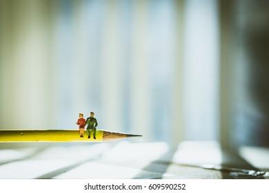 Miniature people lover sitting on pencil - Vintage Filter