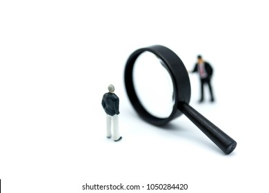 Miniature people: Magnifying glass focusing on the selected of businessman ,recruitment process, HR, HRM, HRD concepts.