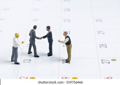 miniature people make handshaking agreement on calendar background