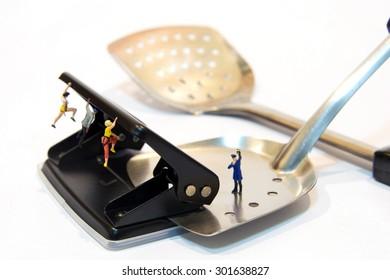 miniature people making hold on spatula