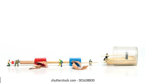 miniature people making tooth stick from pencil